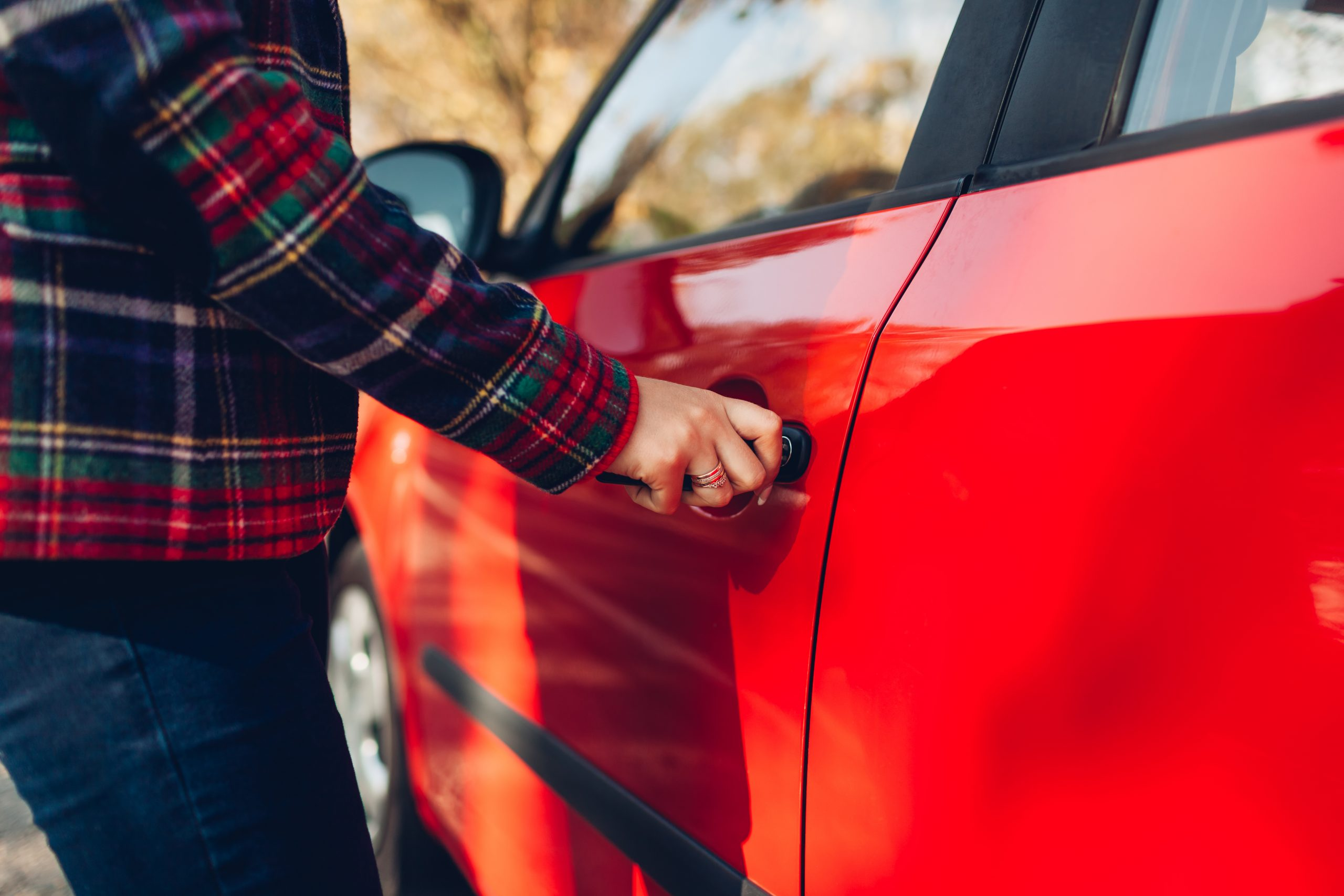 Opening car door. Woman opens red car with key on autumn road. Driver locks door up