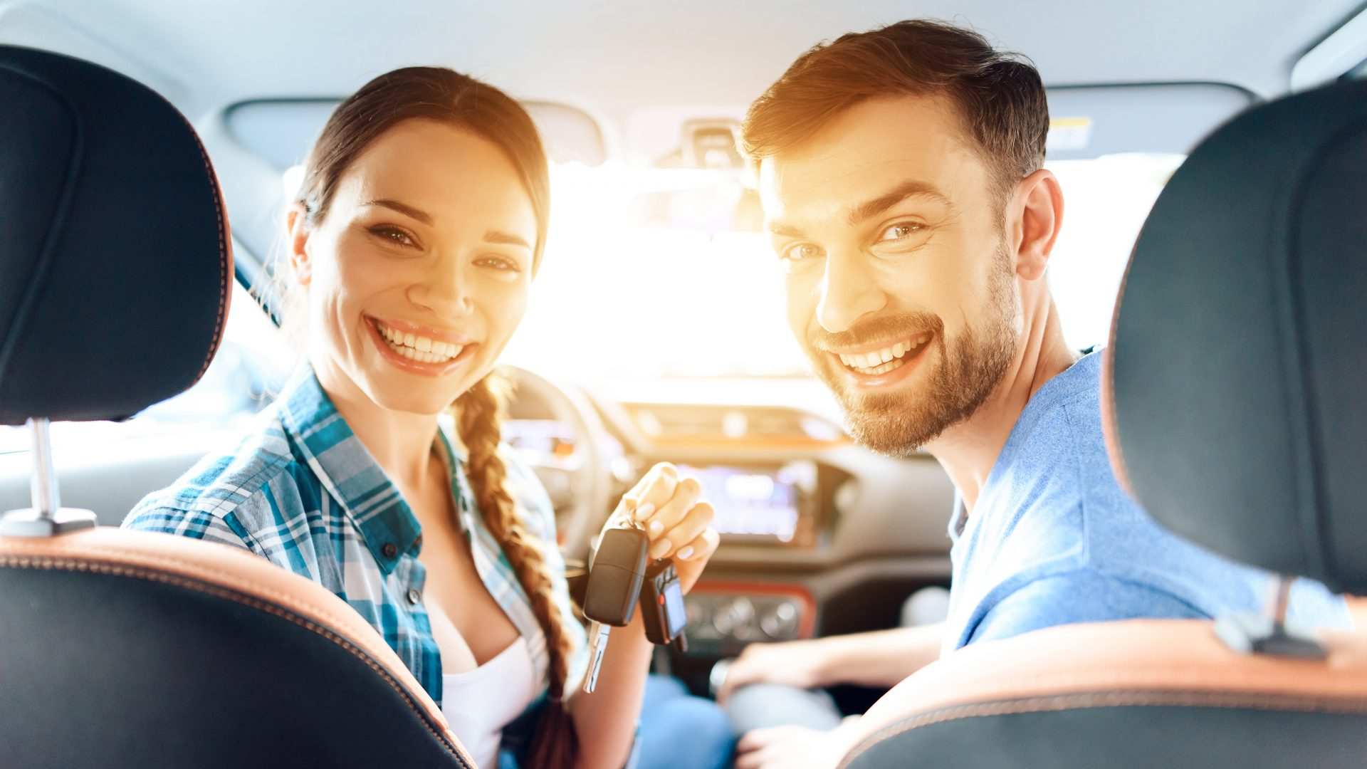 Girl and the guy are sitting in a new car and smiling.